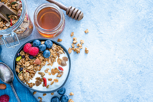 Healthy eating: black bowl with homemade yogurt and granola shot from above on blue table. The bowl sitting on a blue napkin and a honey jar and honey dipper are visible at the top left. Cinnamon sticks, berries and almonds complete the composition. The composition is at the left of an horizontal frame leaving useful copy space for text and/or logo at the right. Predominant color is blue. High resolution 42Mp studio digital capture taken with Sony A7rii and Sony FE 90mm f2.8 macro G OSS lens