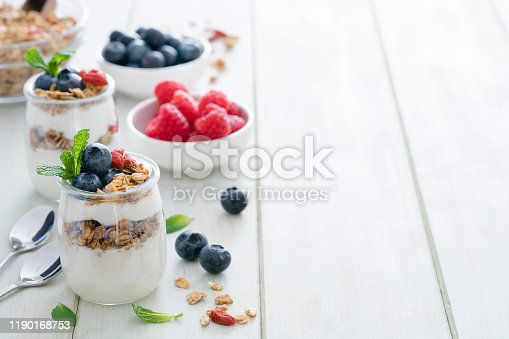 Healthy eating: two glass containers with homemade yogurt and granola shot on breakfast table. Two spoons are beside the yogurt containers. Some berries complete the composition. The composition is at the left of an horizontal frame leaving useful copy space for text and/or logo at the right. Predominant color is green. High resolution 42Mp studio digital capture taken with Sony A7rii and Sony FE 90mm f2.8 macro G OSS lens