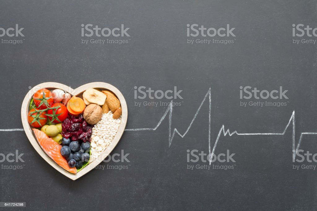 Alimentos saludables en corazón y cardiógrafo en Resumen médico de pizarra - foto de stock