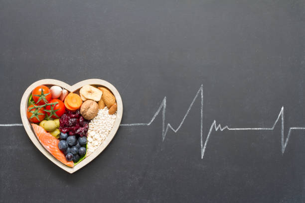 Healthy food in heart and cardiograph on blackboard medical abstract stock photo