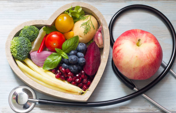 healthy food in heart diet concept with stethoscope - mangiare sano foto e immagini stock