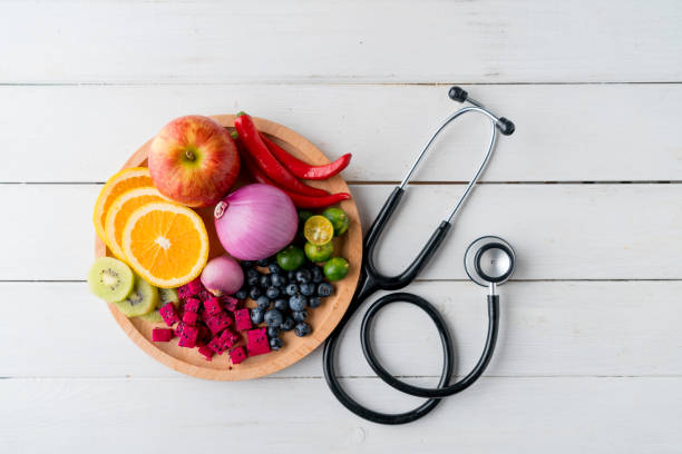 Healthy food in heart dish with doctor's stethoscope Healthy food in heart dish with doctor's stethoscope cholesterol stock pictures, royalty-free photos & images