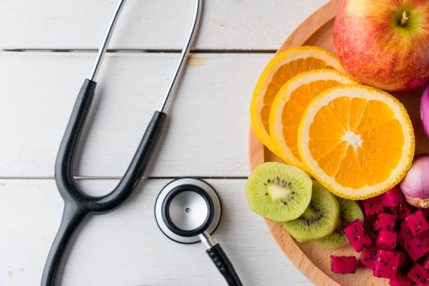 Healthy food in heart dish with doctor's stethoscope stock photo