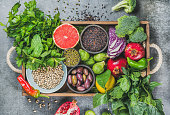 Healthy food in rustic wooden tray over grey background