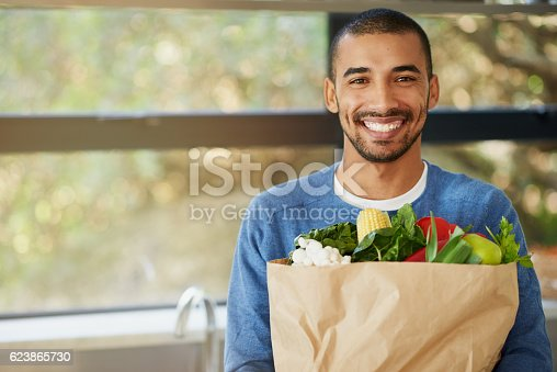 Portrait of a happy young man holding a bag full of healthy vegetables at homee