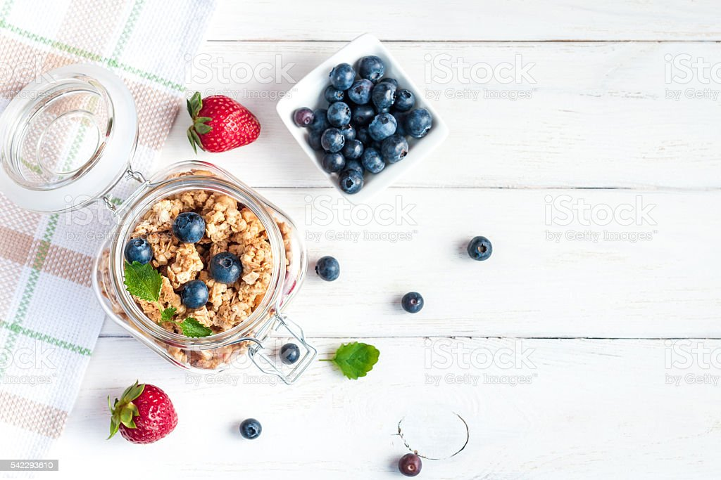 Healthy food. Muesli in the jar, blueberries and strawberries stock photo