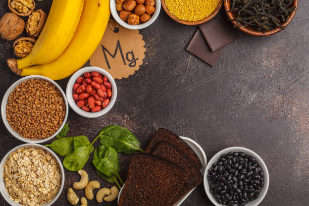 healthy food nutrition dieting concept. assortment of high magnesium sources. banana chocolate spinach, buckwheat, nuts, beans, oat. dark background, copy space - magnesium stock photos and pictures