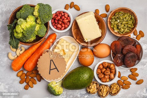 istock Healthy food nutrition dieting concept. Assortment of high vitamin A sources. Carrots, nuts, broccoli, butter, cheese, avocado, apricots, seeds, eggs. White background, top view 950608692