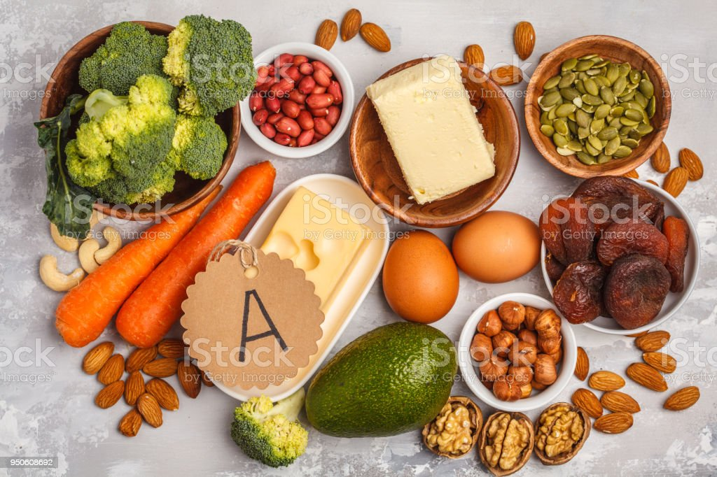 Healthy food nutrition dieting concept. Assortment of high vitamin A sources. Carrots, nuts, broccoli, butter, cheese, avocado, apricots, seeds, eggs. White background, top view stock photo
