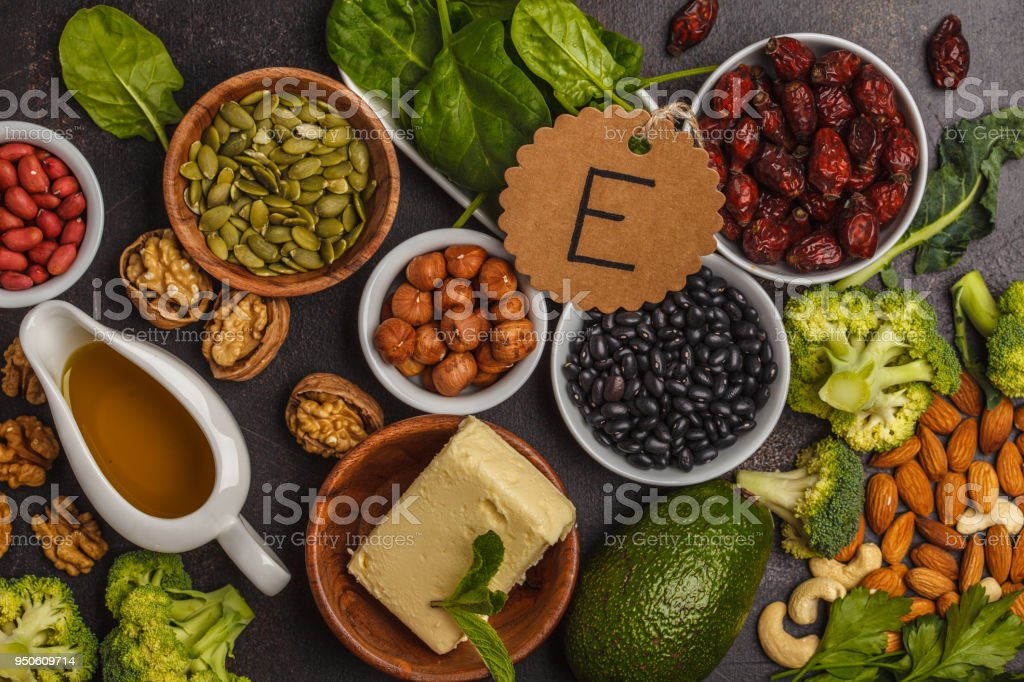 Healthy food nutrition dieting concept. Assortment of high vitamin E sources. Oil, nuts, avocado, butter, healthy fats, rose hips, parsley, seeds, spinach. Dark background, top view stock photo