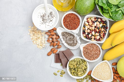 istock Healthy food nutrition dieting concept. Banana, chocolate, spinach, avocado, apple, quinoa, chia, flax seeds, yogurt, almond, beans, oat, pumpkin seeds, olive oil. 907861920