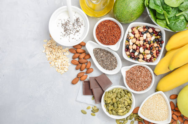 healthy food nutrition dieting concept. banana, chocolate, spinach, avocado, apple, quinoa, chia, flax seeds, yogurt, almond, beans, oat, pumpkin seeds, olive oil. - magnesium stock photos and pictures