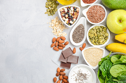 istock Healthy food nutrition dieting concept. Banana, chocolate, spinach, avocado, apple, quinoa, chia, flax seeds, yogurt, almond, beans, oat, pumpkin seeds, olive oil. 907861926