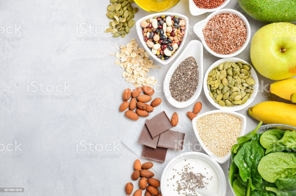 Healthy food nutrition dieting concept. Banana, chocolate, spinach, avocado, apple, quinoa, chia, flax seeds, yogurt, almond, beans, oat, pumpkin seeds, olive oil. stock photo