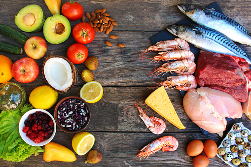 Healthy food of animal and vegetable origin on old wooden background. Concept of proper nutrition. Top view. Flat lay.