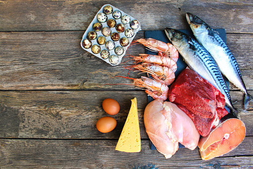 Healthy food of animal origin on old wooden background. Concept of proper nutrition. Top view. Flat lay.