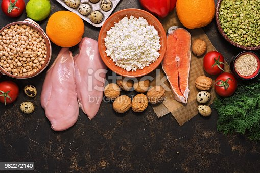 istock Healthy food on a dark background, salmon, chicken fillet, fruits, vegetables, cereals, cottage cheese. Top view, space for text. The concept of healthy eating. 962272140