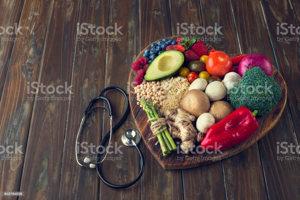 Healthy food on a heart shape cutting board. stock photo
