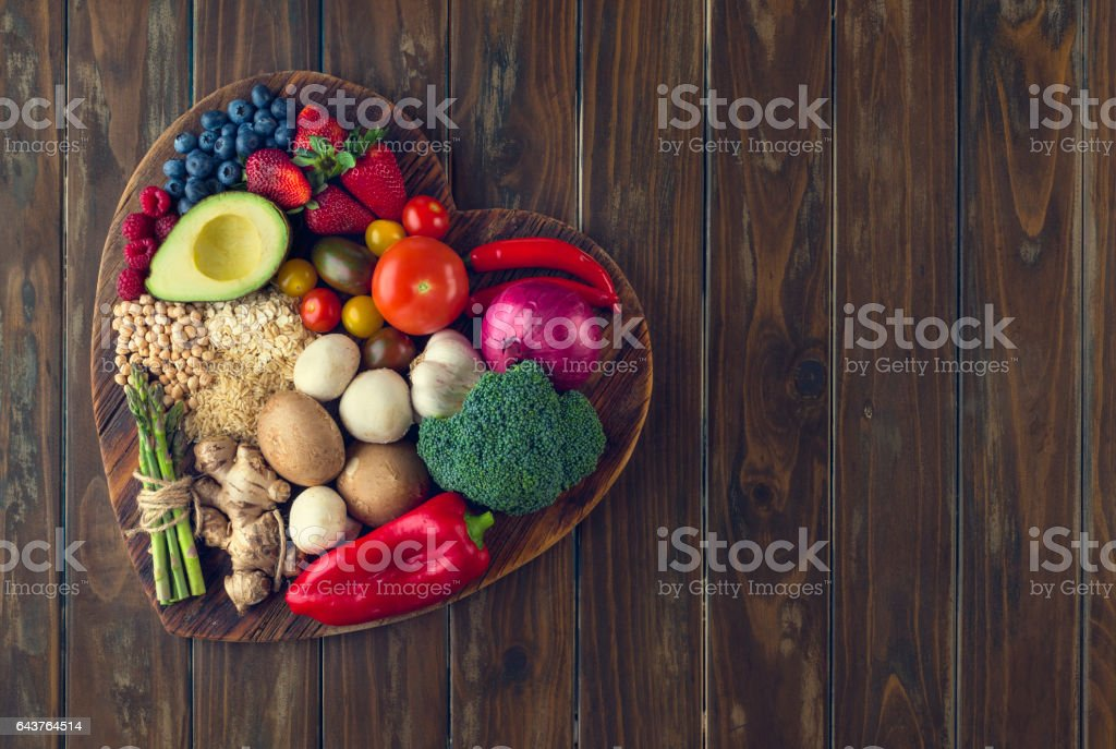 Healthy food on a heart shape cutting board stock photo