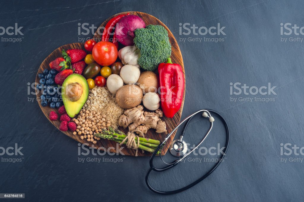 Healthy food on a heart shape cutting board. stock photo