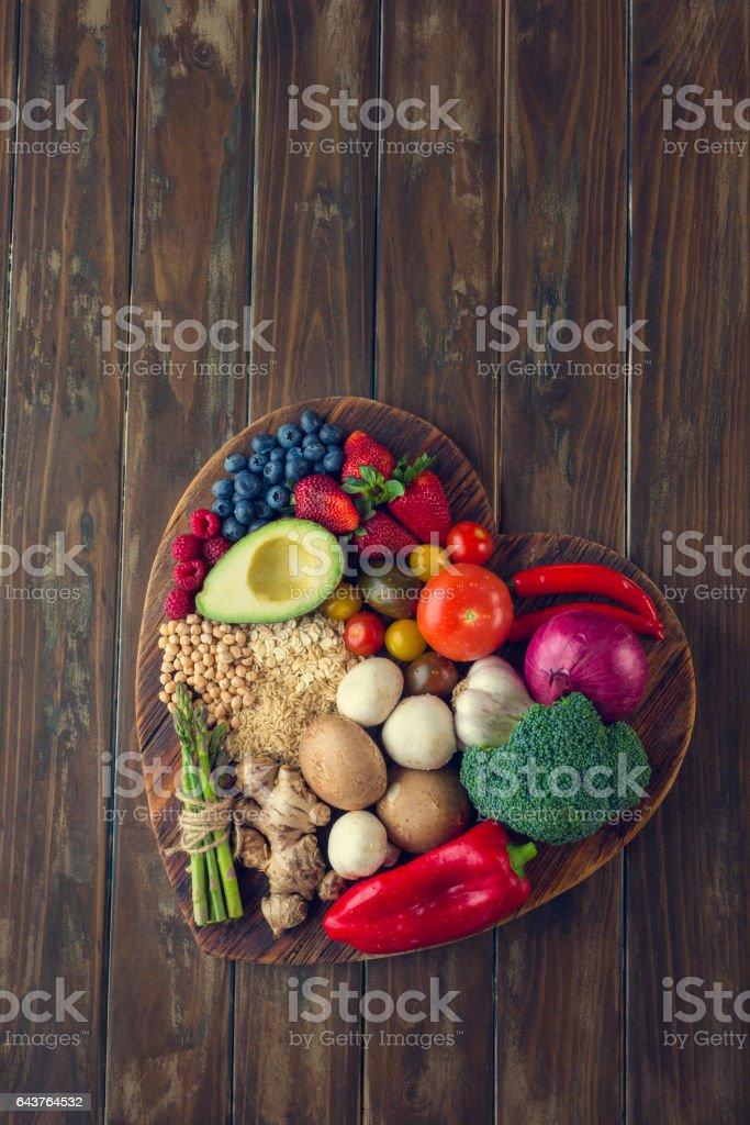 Alimentos saludables en una tabla de cortar de forma de corazón - foto de stock