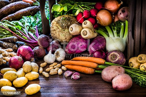 Front view of a large group of multicolored fresh organic roots, legumes and tubers shot on a rustic wooden background. The composition includes potatoes, Spanish onions, ginger, purple carrots, yucca, beetroot, garlic, peanuts, red potatoes, sweet potatoes, golden onions, turnips, parsnips, celeriac, fennels and radish. Some elements are on a rustic wooden crate. Low key DSLR photo taken with Canon EOS 6D Mark II and Canon EF 24-105 mm f/4L