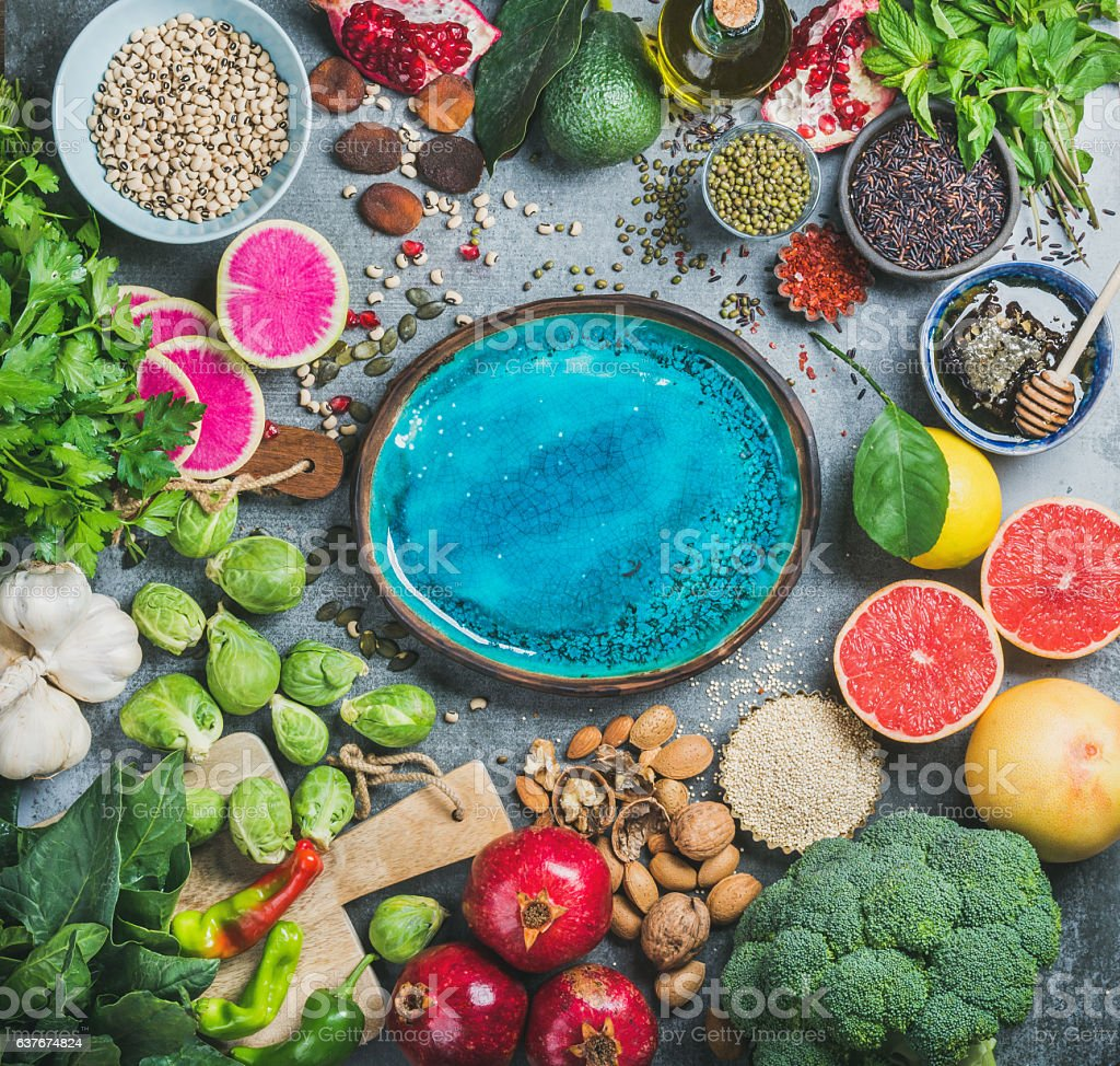 Healthy food over grey background, bright blue plate in center