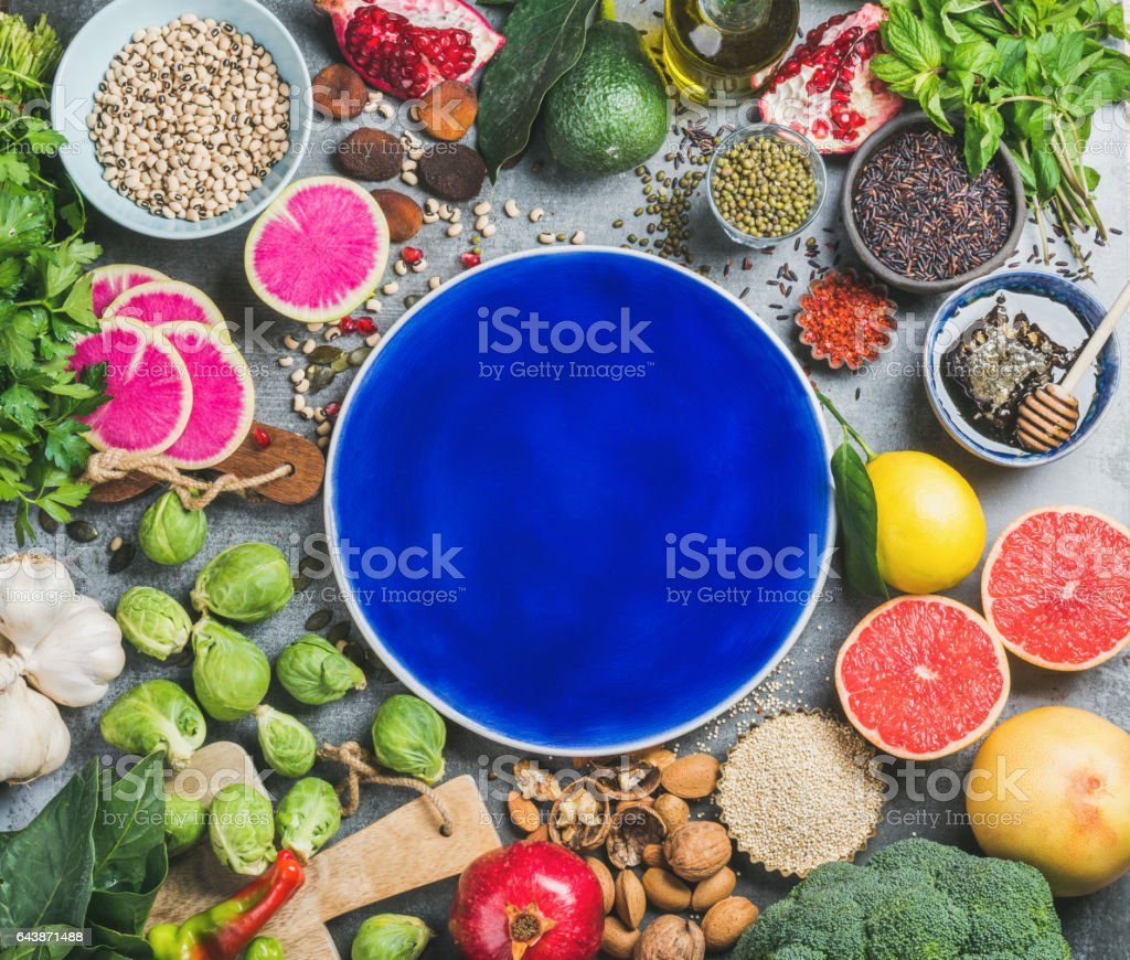 Healthy food over grey background, dark blue plate in center