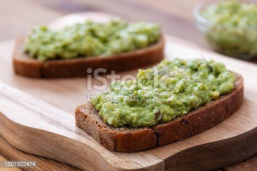 Healthy food. Rye bread with guakomole, avocado pasta on wooden cutting board. Avocado toast for breakfast isolated.