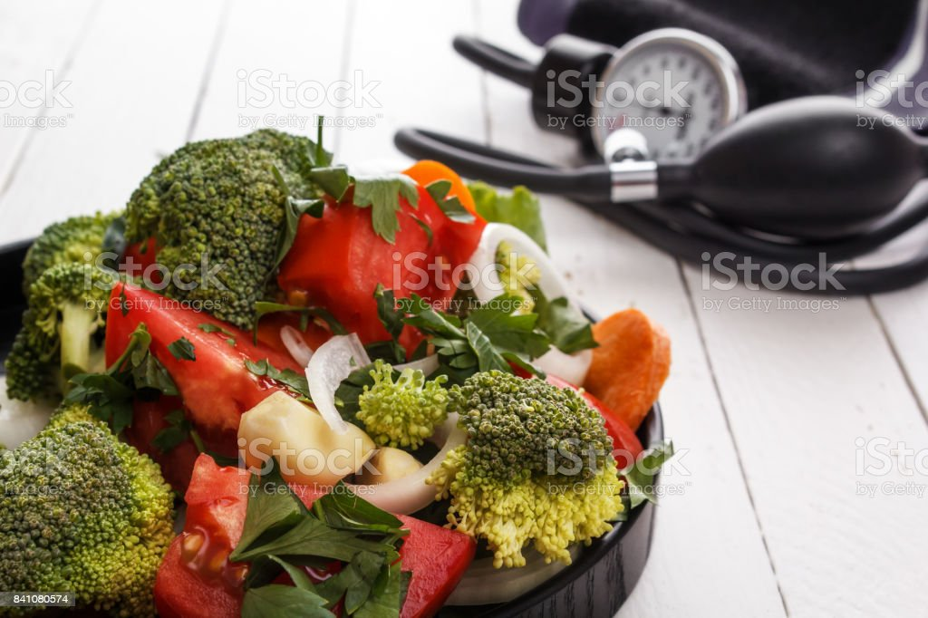 Healthy food salad from vegetables and a tonometer on white boards stock photo