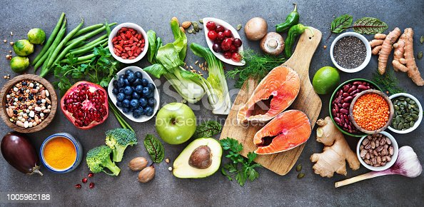 Healthy food selection: food sources of omega 3 and unsaturated fats, fruits, vegetables, seeds, superfoods with high vitamin e and dietary fiber, cereals on gray background