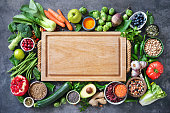 Healthy food selection with fruits, vegetables, seeds, super foods, cereals and the cutting board in the middle as copy space
