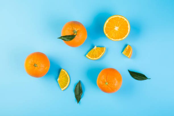 Healthy food. Sliced orange with green leaves on blue background, top view Slices of orange with leaves orange fruit stock pictures, royalty-free photos & images