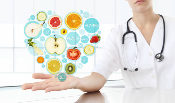 healthy food supplements concept, Hand of nutritionist doctor showing symbols fruits in hearth shape stock photo