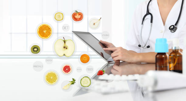 healthy food supplements concept, Hand of nutritionist doctor touch digital tablet on symbols fruits background stock photo