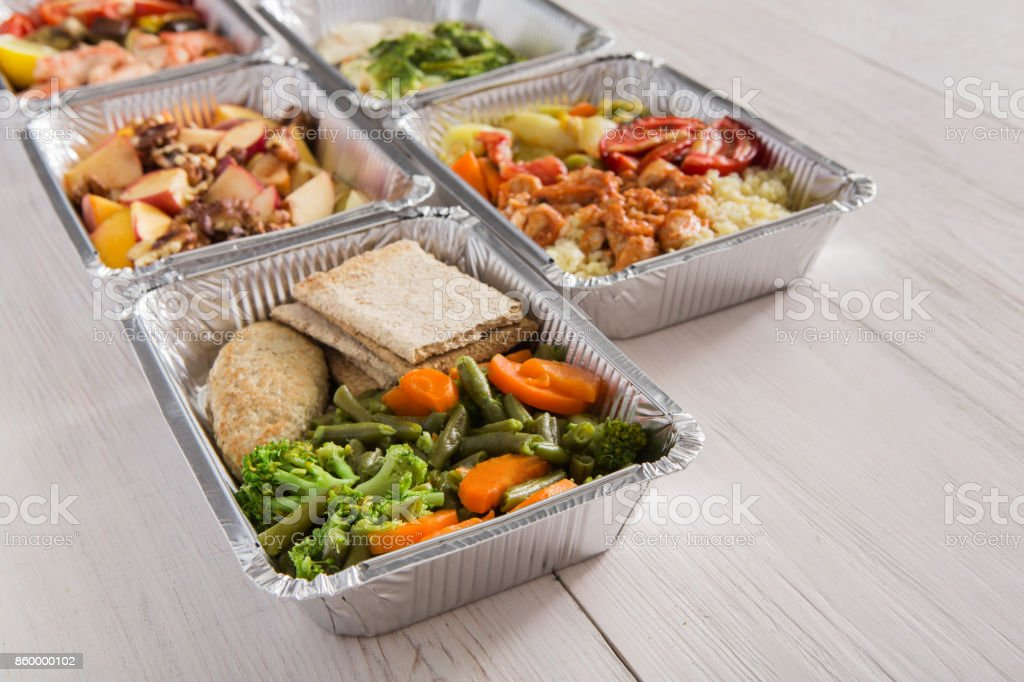 Healthy food take away in foil boxes on wood background stock photo