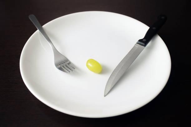 Gesundes Lebensmittelthema: grüne Traube auf einem weißen Teller. Gewichtsverlust, gesunder Lebensstil – Foto