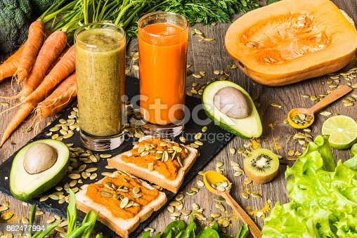 istock Healthy food. Vegan sandwiches with fresh vegetables on wooden background. Detox diet. Different colorful fresh juices 862477994