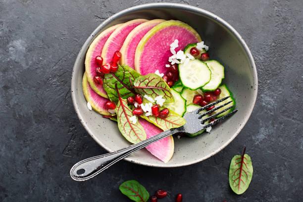gesunde ernährung. wassermelone radieschen, gurken, reis, granatapfelsamen, sorrel, rote adiesensalat in einer schüssel auf dunklem hintergrund. top view. platz kopieren. - radieschen salat stock-fotos und bilder