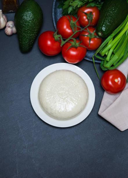 Gesunde seradienende Nahrung. Weißer Weichkäse. Milchprodukte und Gemüse auf dunklem Hintergrund – Foto