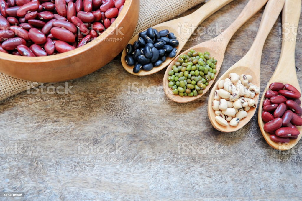 Healthy food with whole grains is red beans,soy beans,black turtle bean,mung bean in wooden spoons and wooden cups on the old wooden table. above view cereal and copy space for add messages. stock photo