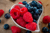 healthy foods and good eating habits concept with a heart shaped white bowl of blueberries and raspberries spilt in the middle, half blueberry half raspberry with berries and burlap in the background