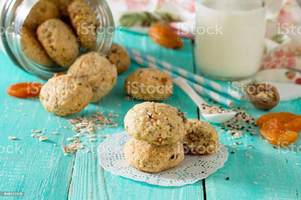 Healthy foods for breakfast. Homemade biscuits from oat flakes with sesame seeds, dried fruits, nuts in an open glass jar and milk on a wooden background. Healthy food concept. stock photo