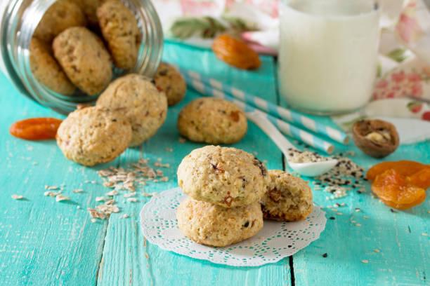gesunde lebensmittel für das frühstück. hausgemachte kekse aus haferflocken mit sesam, getrocknete früchte, nüsse in einem offenen glas und milch auf einem hölzernen hintergrund. gesunde ernährung-konzept. - haferflocken rosinen stock-fotos und bilder