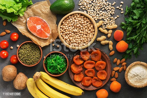 istock Healthy foods high in potassium. A variety of legumes, salmon, fruits, vegetables, dried apricots, seaweed chuka and nuts on a dark background. Top view, flat lay. 1152451395