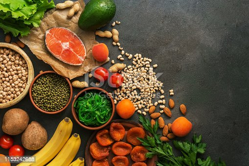 istock Healthy foods high in potassium. A variety of legumes, salmon, fruits, vegetables, dried apricots, seaweed chuka and nuts on a dark background. Top view, flat lay. 1153242688