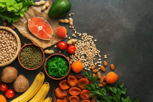 gezonde voedingsmiddelen met een hoog kaliumgehalte. een verscheidenheid van peulvruchten, zalm, fruit, groenten, gedroogde abrikozen, zeewier en moeren op een donkere achtergrond. bovenaanzicht, plat lag. - kalium stockfoto's en -beelden