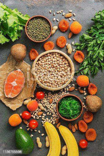 istock Healthy foods high in potassium. A variety of legumes, salmon, fruits, vegetables, dried apricots, seaweed chuka and nuts on a dark background. Top view, flat lay. 1156755598