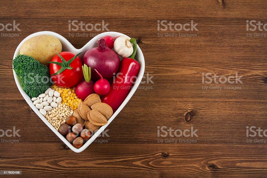 Alimentos saludables en corazón forma de plato en la mesa de madera - foto de stock