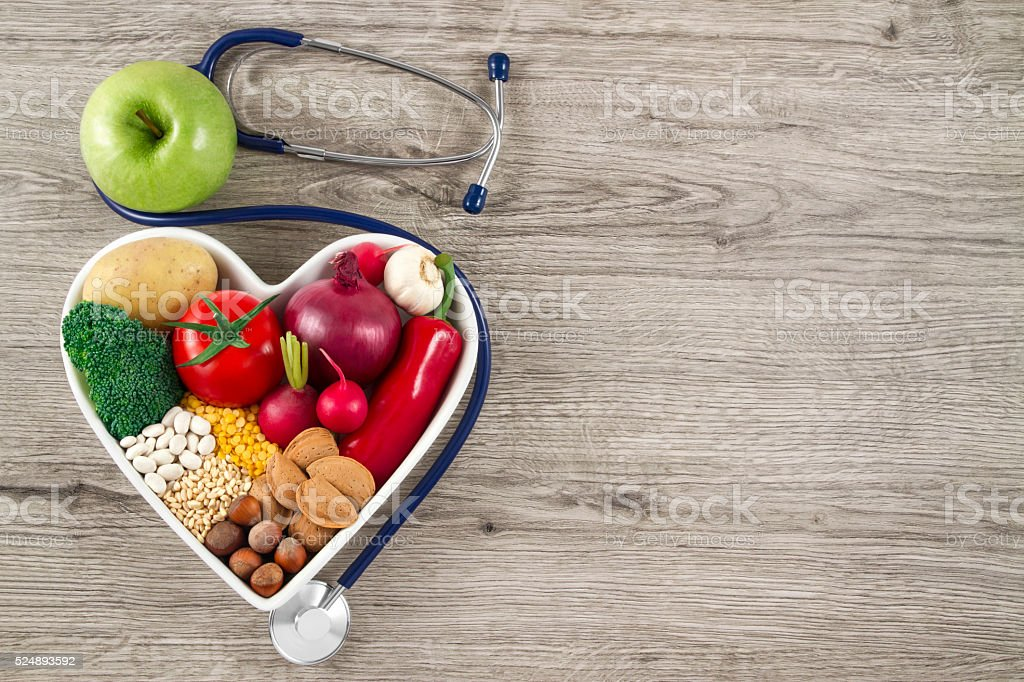 Healthy Foods in Heart Shaped with Stethoscope on Wooden Background stock photo